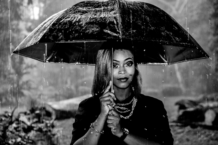 black and white portrait of a girl holding an umbrella - rain photography tips
