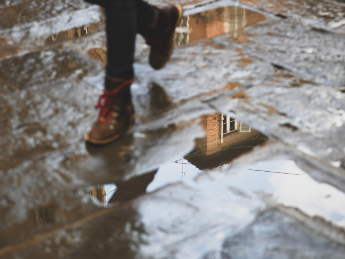 Atmospheric rain photo of a persons feet walking through puddles on the street