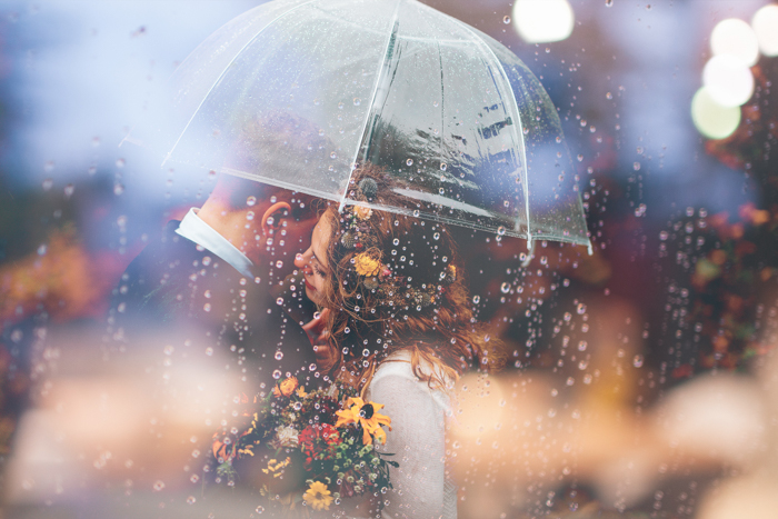 Dreamy wedding photography of a couple embracing under an umbrella - rain pictures
