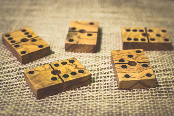 close up of five wood domino tiles on a brown table