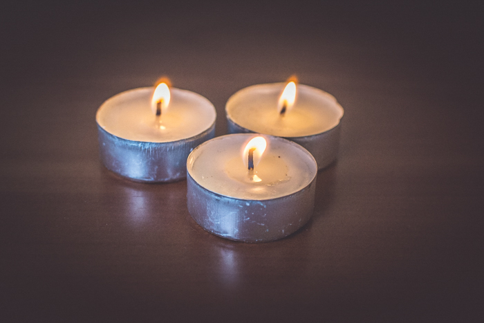 close up of three lit tealight candles