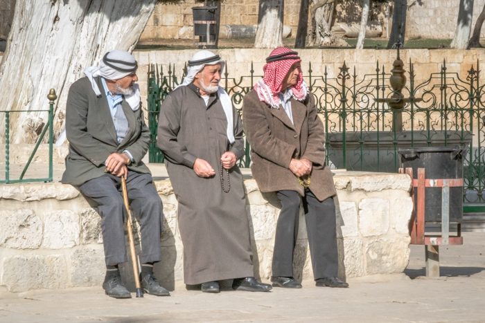 three arab men relaxing sitting by a fountain on a sunny afternoon