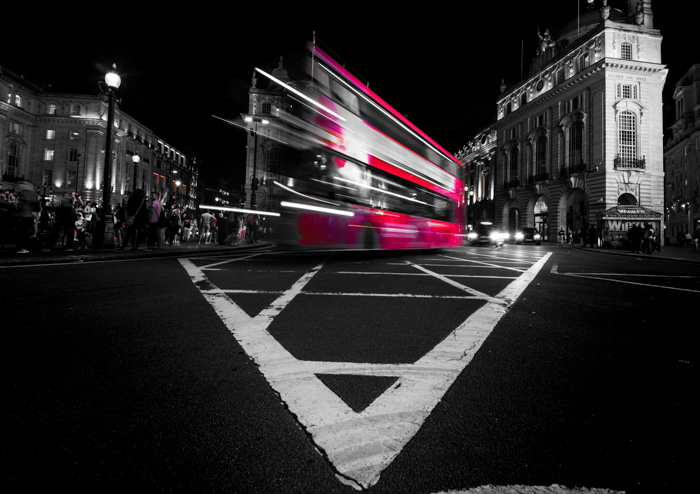 moving red double decker bus on a night street. selective color red applied