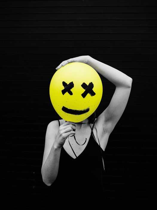 black and white photo of woman holding yellow balloon with a face drawn on it in front of her face. selective color yellow applied.