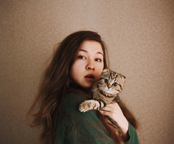 Artistic portrait of a female model posing with a stripy cat - creative selfies