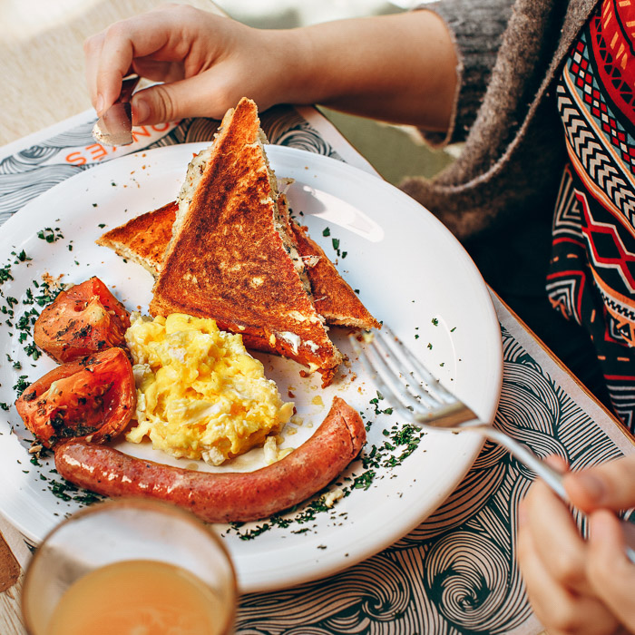 A smartphone food photography shot of a person eating a scrumptious looking brunch at a table