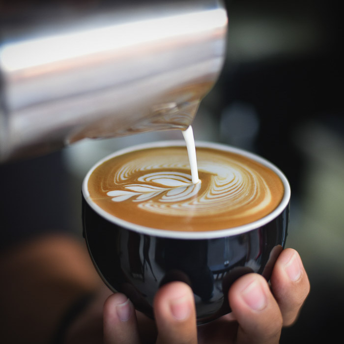 A smartphone food photography shot of a person pouring milk into a coffee