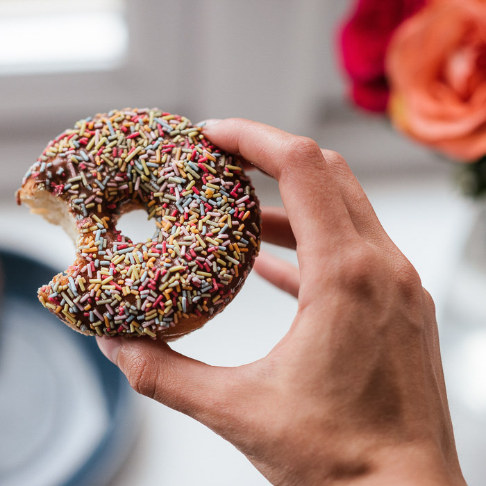 A person holding a chocolate sprinkled doughnut with a bite taken out of it