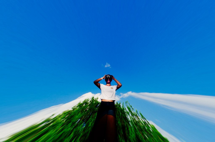 abstract photo of a man in a white shirt posing in front of dark green trees and bright blue sky