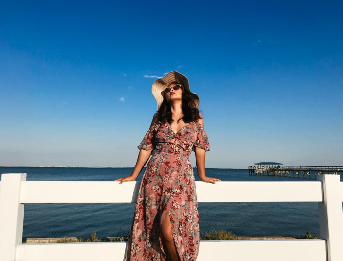 woman in a summer maxidress, sunglasses, and large sun hat, leaning on a white fence, the blue sea and sky behind her