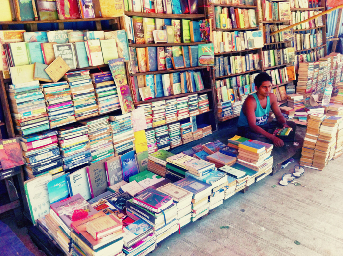 A smartphone street photography shot of a vendor looking after his book stall