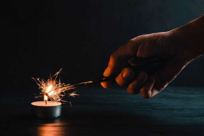 hand holding sparkler in a dark room, lighting the sparkler with a tealight candle