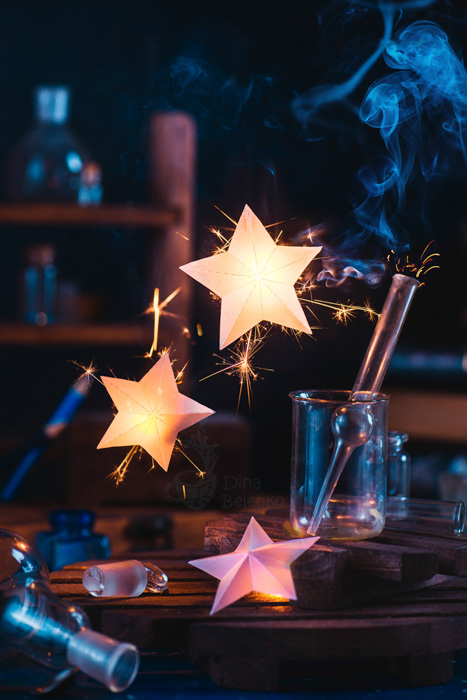 Stars and test tubes in a dark room lit with sparkler photography