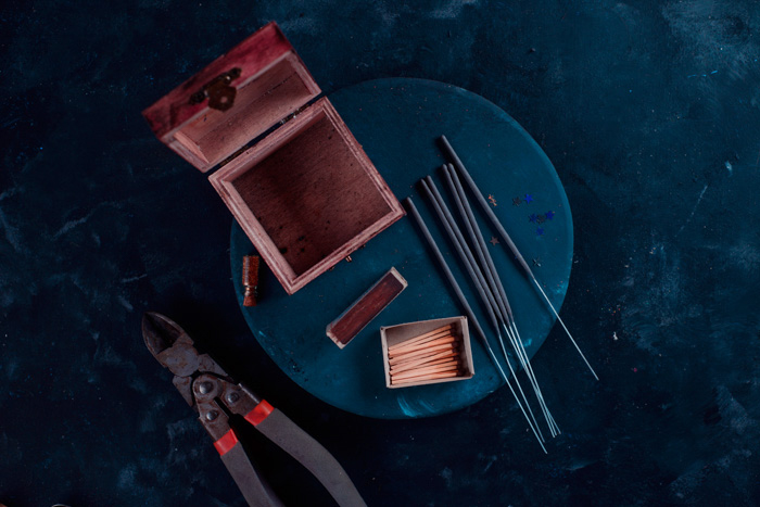 A flat lay of an empty open wood box, sparklers, matches and wire cutter on a table