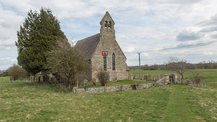 A small stone church in a countryside landscape with a visual anchor selected and highlighted in red