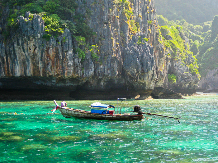 wooden boat on crystal blue green waters in Thailand