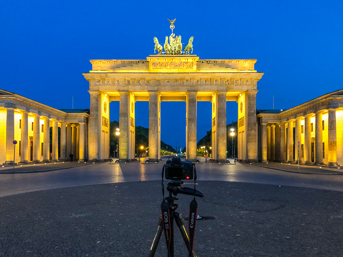 Brandenburg gate at night, lit up by yellow lights, a camera set up on a tripod in front of it - great travel photography destinations