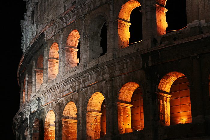 the Colosseum in Italy, lit from within with a warm orange yellow light, glowing in the night
