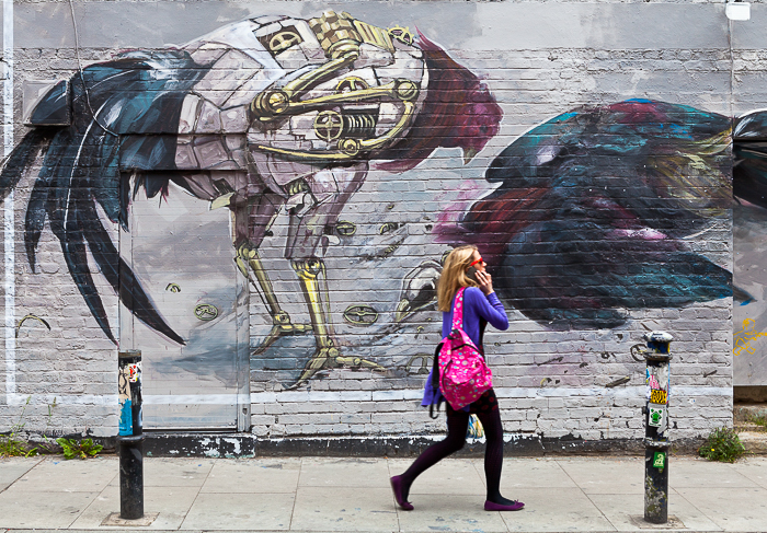 blonde girl in a pink scarf, talking on the phone as she walks past a wall with street art graffiti - travel photography destinations