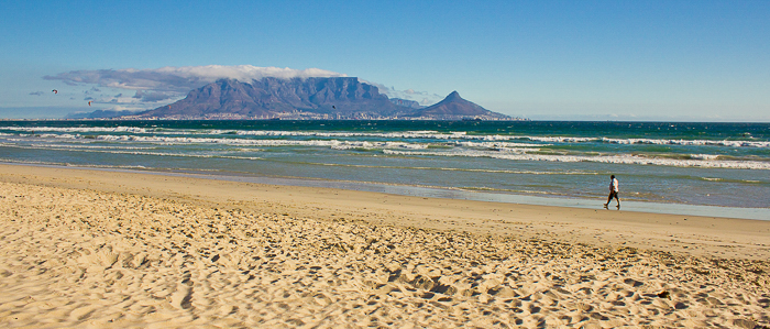 a man walking along the shore at a beach in Cape Town