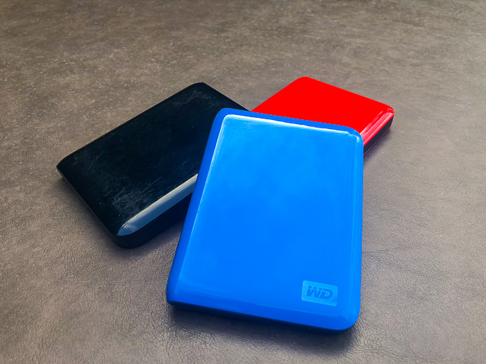 three external hard disk drives on a grey surface - travel safety tips for photographers