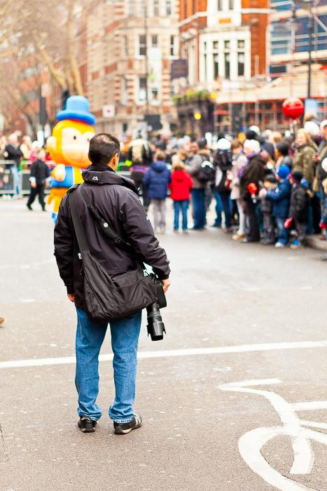 Fotógrafo de viagem em um casaco preto segurando uma câmera DSLR e observando as pessoas em um desfile à distância.