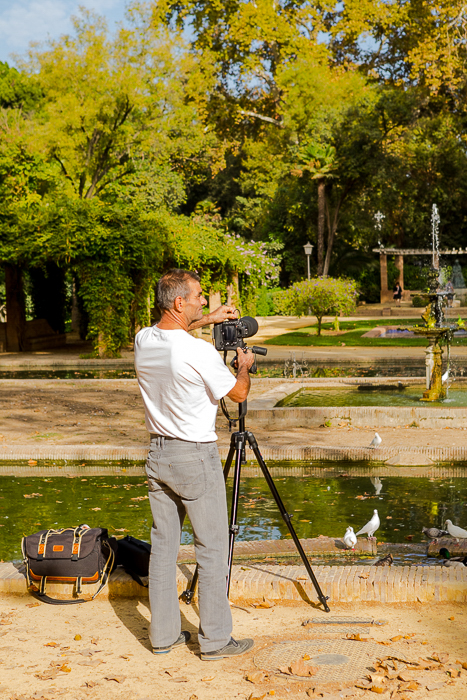 photo from behind of a man setting up a DSLR on a tripod by a pond with white birds, the trees in the distance - travel safety tips
