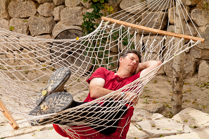 man in a red shirt sleeping in a hammock outdoors, a stone wall in the background - travel safety tips for photographers
