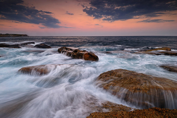 waters rushing over flat brown rocks at Coogee Beach, Sydney, Australia, an orange sunset sky on the horizon