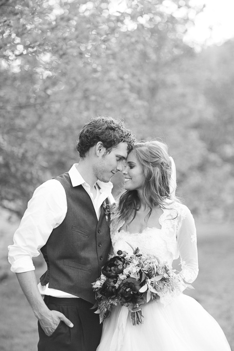 black and white photo of newly weds standing outdoors, gazing into each others eyes, foreheads touching
