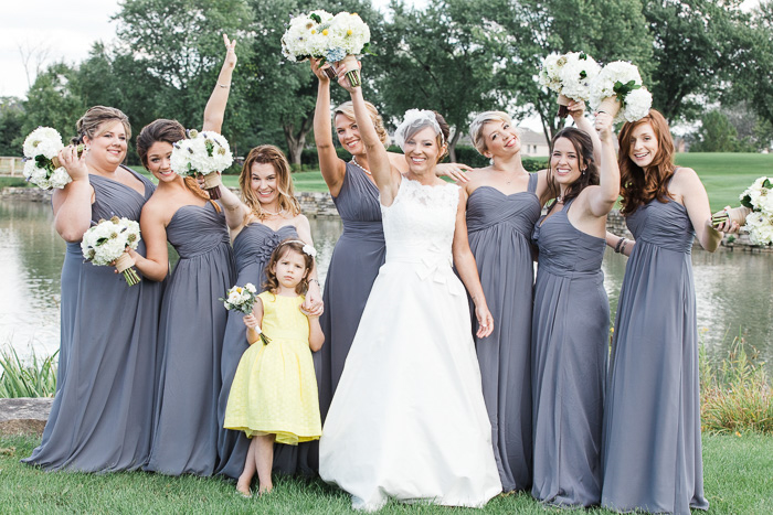 bride with flower girl in yellow and bridesmaids in grey gowns standing in front of a lake smiling and holding their bouquets up