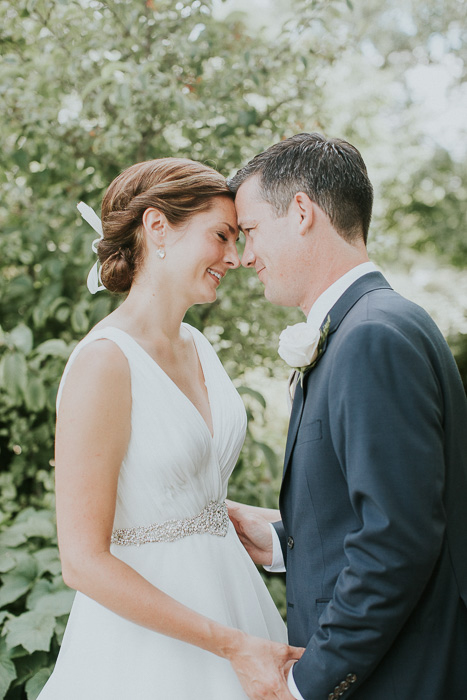desaturated photo of newly weds standing outdoors, their foreheads touching, with the trees behind them