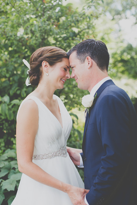 photo of newly weds standing outdoors, their foreheads touching, with the trees behind them, matte effect - wedding photo editing trends