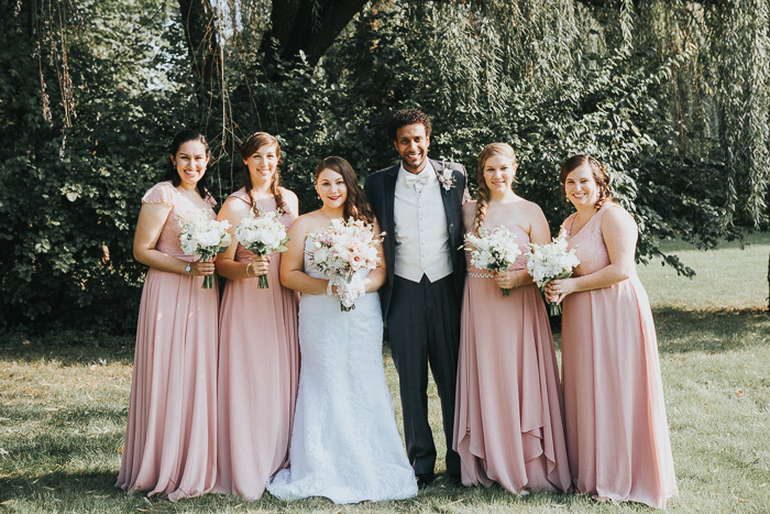 desaturated photo of bride, groom, and bridesmaids in pale pink standing against a backdrop of trees.