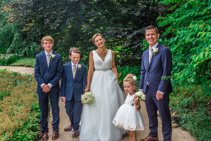 wedding family, bride, groom, and 3 children, standing in a path with bushes and trees behind them, HDR wedding photo editing