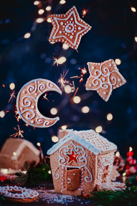A magical Christmas still life photography shot of a gingerbread house and floating cookies