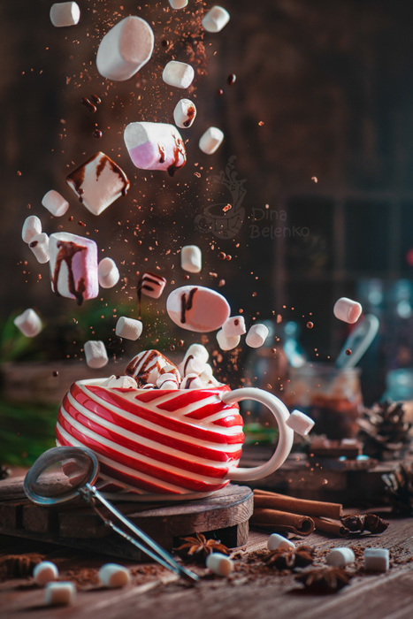 A magical Christmas photography still life of a coffee cup and levitating marshmallows
