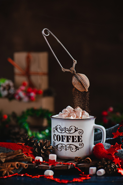 A magical Christmas still life photography shot of a coffee cup of marshmallows and levitating chocolate sprinkler