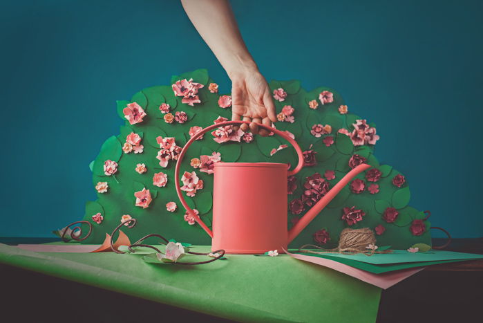 Fun photography still life of a person holding a craft watering can featuring opposite colors red and green