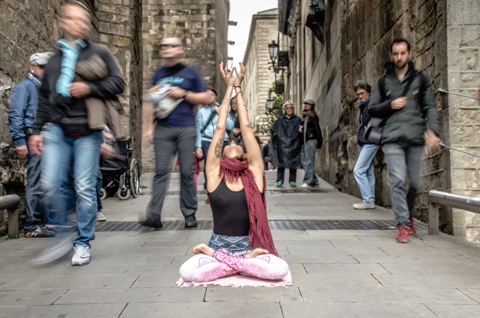 A girl in a yoga pose in the middle of a busy street - DSLR basics for photography beginners