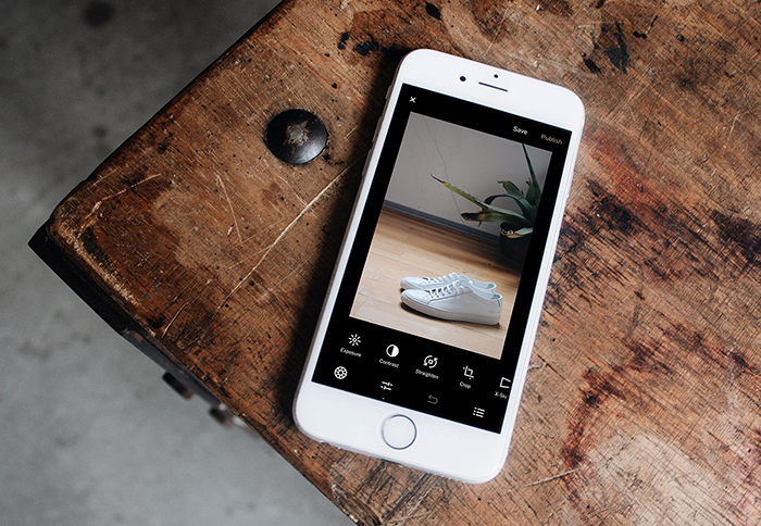 A smartphone on a wooden table - best apps to put backgrounds on pictures