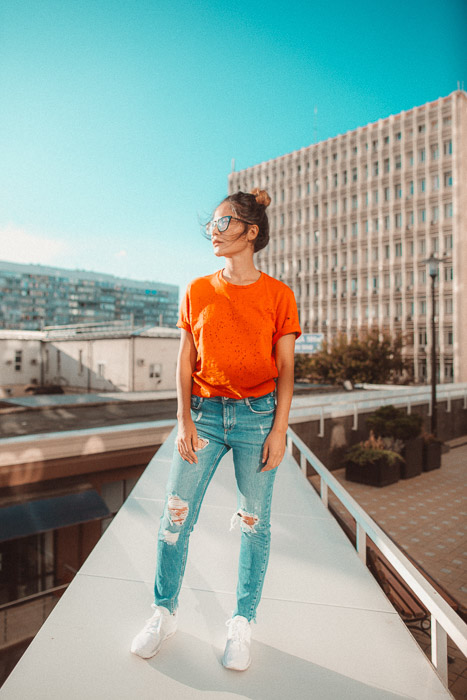 An artistic fashion photography shoot featuring a female model and orange and blue color scheme