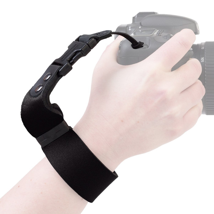 Visual of a hand holding a DSLR camera attached to the OP/TECH SLR Wrist Strap for DSLR cameras
