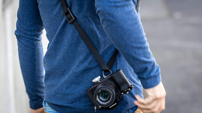 A photographer with his camera and Luma Loop 3 Sling Strap - best camera strap