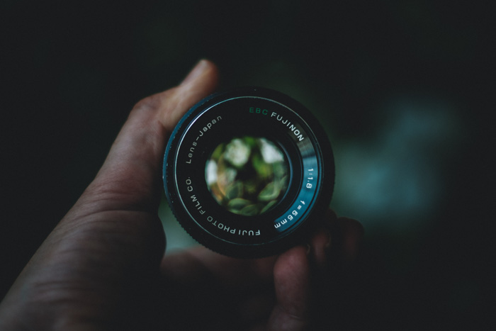 A close up of a photographer holding one of the best Fuji lenses