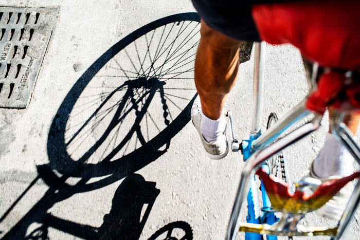 A close up of a cyclist pedalling with shadows cast on the stone ground, best time of day for photos