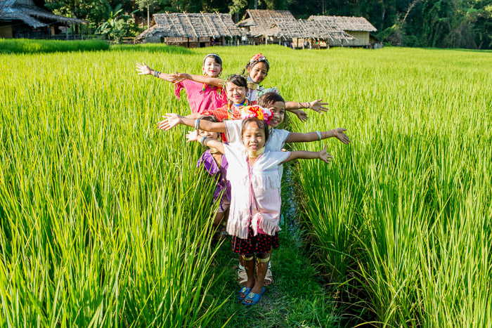 Natural Light Photography shot of a group of kids posing in a rice paddy field - best time to take photos outdoors