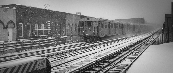 A black and white fine art photo of a train arriving at the platform in winter in Brooklyn, New York.