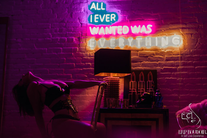 A boudoir photography model posing sensually indoors in front of a neon sign - tips for boudoir clients