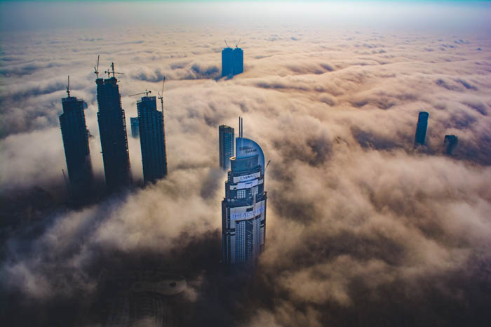 An aerial view of tall skyscrapers bursting through clouds - cloudy day photography